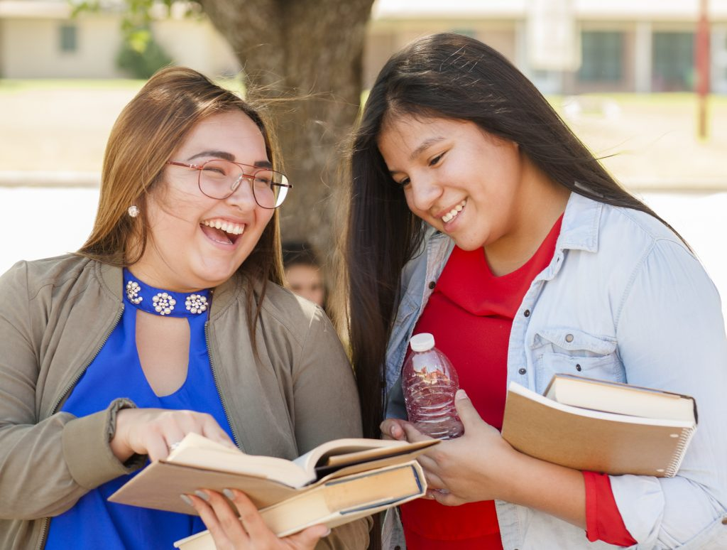 Multi-ethnic group of high school or college girls talking together on campus outdoors in summer or spring season.  The Hispanic and Native American group of girls are holding textbooks and backpacks.  The school building is in the background. Another girl is sitting by tree.